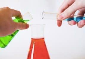 eine giftgrüne und eine blaue Flüssigkeit werden in einen Erlenmeierkolben mit roter Flüssigkeit gekippt. Alex Kondratiev