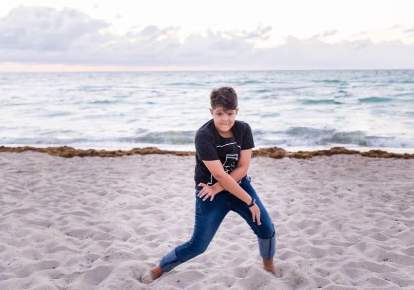 Jugendlicher posiert am Strand